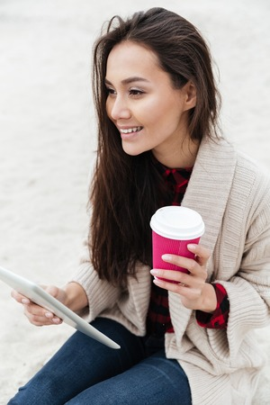 Picture of happy caucasian lady sitting outdoors at beach wearing warm jacket using tablet computer. Looking aside and drinking coffee.