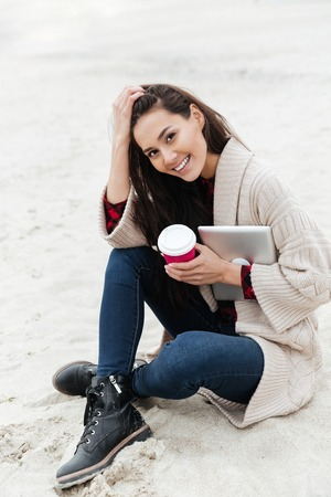 Picture of smiling caucasian woman sitting outdoors at beach wearing warm jacket holding tablet computer. Looking at camera drinking coffee.