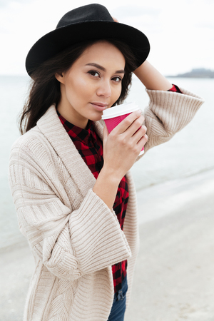 Photo of amazing young caucasian lady walking outdoors at beach wearing warm jacket drinking coffee. Looking at camera. Stok Fotoğraf