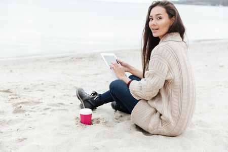 Photo of beautiful young caucasian lady sitting outdoors at beach wearing warm jacket using tablet computer. Looking at camera.