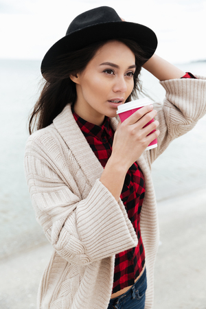 Image of pretty young caucasian lady walking outdoors at beach wearing warm jacket drinking coffee. Looking aside.