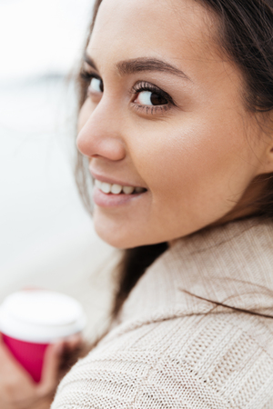 Image of cheerful young caucasian lady walking outdoors at beach wearing warm jacket drinking coffee. Looking at camera.