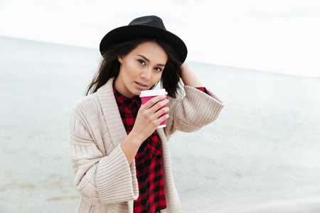 Photo of amazing young caucasian lady walking outdoors at beach wearing warm jacket drinking coffee. Looking at camera. Imagens