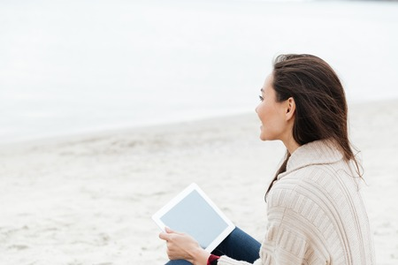 Image of young caucasian lady sitting outdoors at beach wearing warm jacket using tablet computer. Looking aside and drinking coffee.