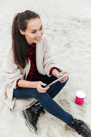 Image of cheerful caucasian lady sitting outdoors at beach wearing warm jacket using tablet computer. Looking aside and drinking coffee.