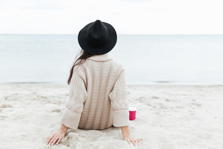 Back view photo of caucasian lady sitting outdoors at beach wearing warm jacket and hat.