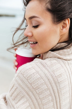 Picture of pretty young caucasian lady walking outdoors at beach wearing warm jacket drinking coffee. Looking aside. Imagens