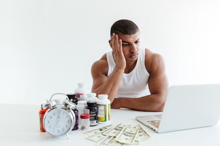 랩톱 컴퓨터를 사용하는 동안 돈과 스포츠 영양 근처 흰색 배경 위에 앉아 슬픈 젊은 스포츠맨의 사진. 옆으로보고.