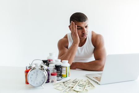Photo of sad young sportsman sitting over white background near money and sport nutrition while using laptop computer. Looking aside.