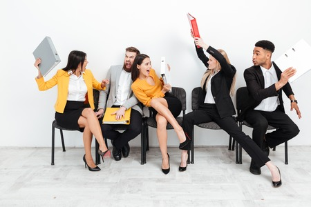 Image of screaming angry colleagues sitting with folders and fighting. Looking aside. Stock Photo