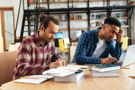 Twee gemengde ras mannelijke studenten die met laptop bestuderen terwijl het zitten bij het bibliotheekbureau