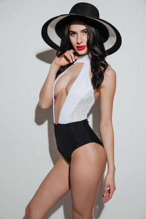 Image of amazing young woman with bright makeup lips wearing hat dressed in swimwear standing isolated. Looking at camera.