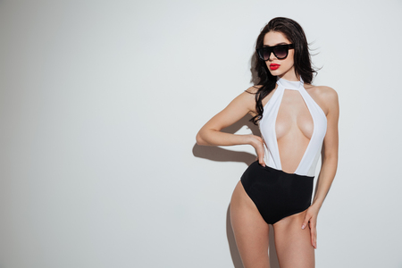 Image of amazing young woman with bright makeup lips dressed in swimwear standing isolated. Looking aside.
