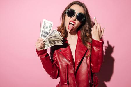 Portret van een arrogant provocerend meisje in de holdingsgeldbankbiljetten van het leerjasje en het tonen van middelvingergebaar dat over roze wordt geïsoleerd