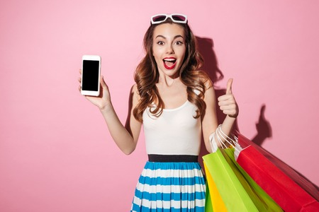 Portrait of a pretty excited girl with colorful shopping bags showing blank screen mobile phone and showing thumbs up gesture isolated over pink background