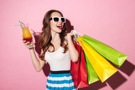 Portrait of a happy smiling girl in sunglasses drinking cocktail and celebrating purchase isolated over pink background