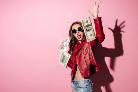 Portrait of a young happy woman winner throwing money banknotes isolated over pink Reklamní fotografie