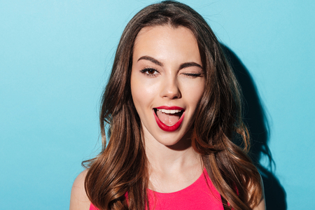 Close up portrait of a pretty young woman winking isolated over blue background 版權商用圖片 - 79834976