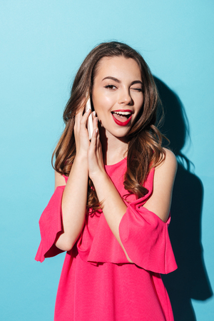 Portrait of a pretty flirty girl in dress winking while talking on mobile phone isolated over blue background Stock Photo
