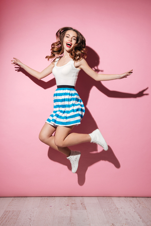 Full length portrait of a happy pretty girl in dress jumping over pink background
