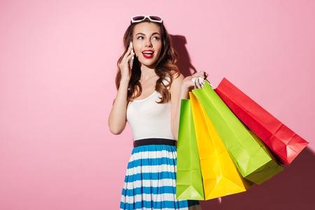 カラフルなショッピング バッグを押しピンク背景に分離された携帯電話で話している笑顔の美しい女性の肖像画