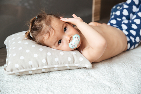 Image of cute little girl child indoors with nipple lies on bed. Looking at camera. Stock Photo