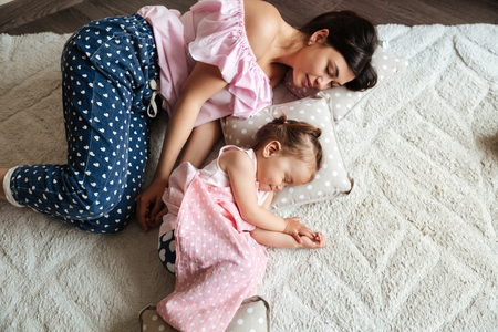 Photo of pretty little girl child indoors with nipple sleeping on bed near mother. Eyes closed.