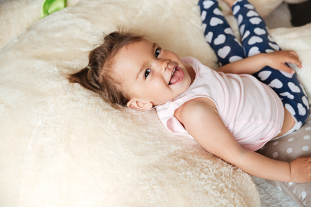 Picture of little cute child girl lies on bed indoors. Looking at camera. Stock Photo