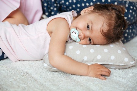Picture of pretty little girl child indoors with nipple lies on bed with mother. Looking aside.