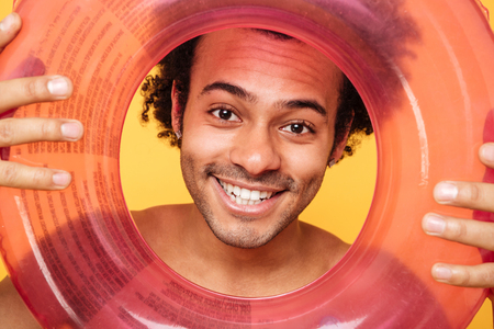 Close up portrait of a cheerful smiling african man in summer clothes holding inflatable ring and looking at camera over yellow background