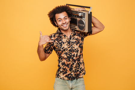 Portrait of a smiling african man in summer clothes holding boombox on his shoulder isolated over yellow background Stock Photo