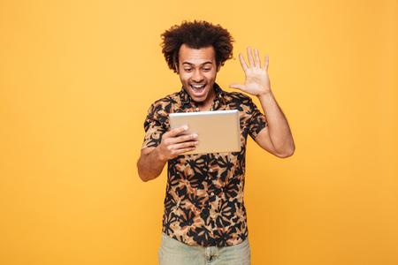 Portret van een opgewekte Afrikaanse mens die videovraag door PC-tablet en golvende die hand hebben over gele achtergrond wordt geïsoleerd Stockfoto