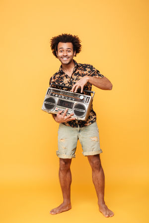 Image of young smiling african man standing with tape recorder isolated over yellow background. Looking at camera. Stock Photo