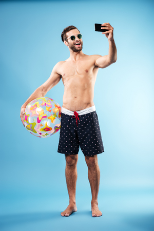 Full length portrait of a happy shirtless guy holding beach ball and making selfie isolated over blue Stock Photo