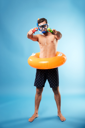 Young bearded serious man in swimming glasses holding water guns and swimmng circle isolated over blue
