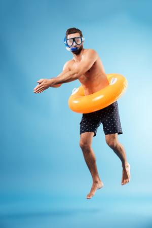 Mens die zwemmende glazen met het zwemmen cirkel duiken draagt die over blauw wordt geïsoleerd