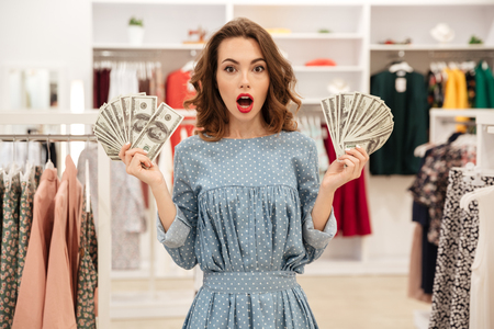 Shocked woman holding big fans of money in hands while standing in shop