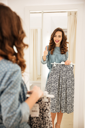 retailer: Image of pretty young lady standing in fitting room and choosing clothes in shop. Looking aside showing thumbs up. Stock Photo