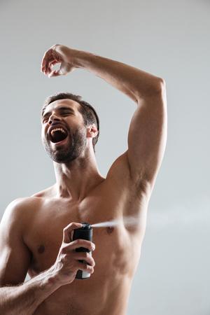 Happy man using deodorant with pleasure isoated