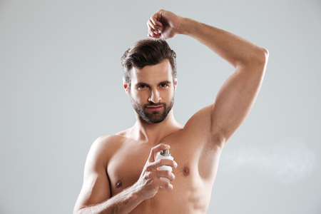 Young serious bearded man looking camera while using perfume isolated Stock Photo