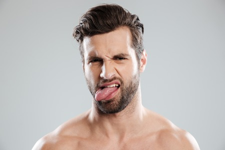 Portrait of an upset irritated naked bearded man showing tongue isolated over white background
