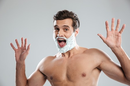 Photo of young screaming man standing isolated over grey background with shaving foam on face. Looking at camera. Stock Photo