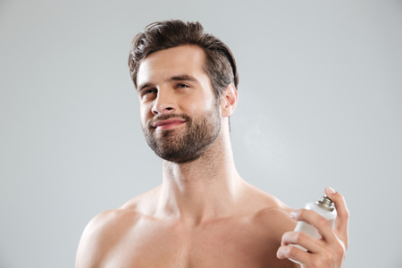 Calm positive man using perfume isolated over grey