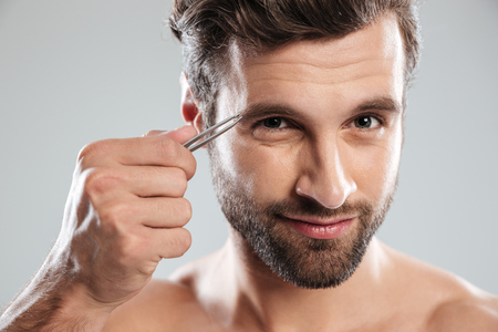 Bearded young man tweezering his eyebrows in the morning isolated over grey Stock Photo