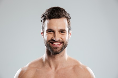 Portrait of a happy young bearded man looking at camera isolated over white background