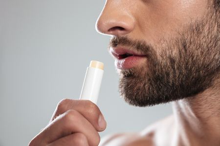Cropped shot of young bearded man with ?olorless lipstick isolated
