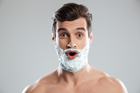 metrosexual: Image of young shocked man standing isolated over grey background with shaving foam on face. Looking at camera.