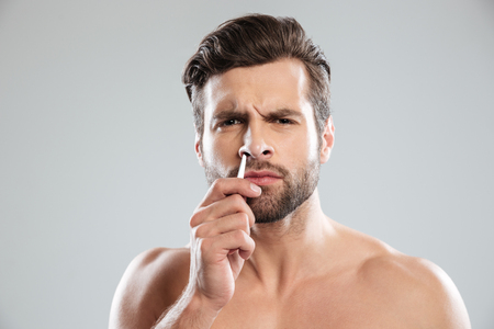Confused bearded man trying to tweezer hair in nose isolated