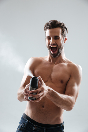 Joyful bearded man playing with deodorant and screaming isolated Stock Photo