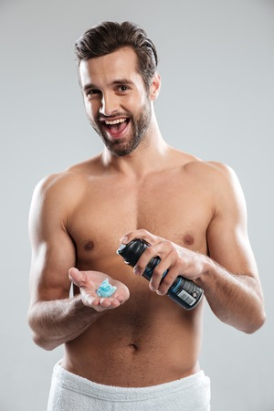 Image of young happy man standing isolated over grey background holding shaving foam. Looking at camera. Stock Photo